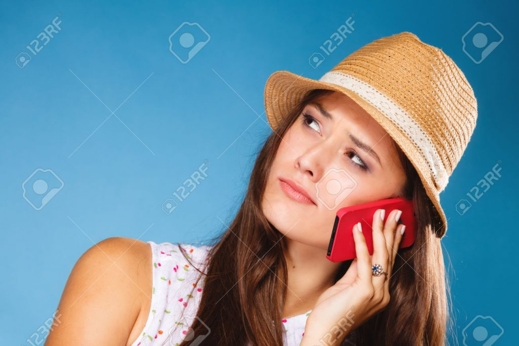 Technology and communication - confused teen girl talking on mobile phone smartphone, worried woman using cell phone on blue. Misunderstanding.